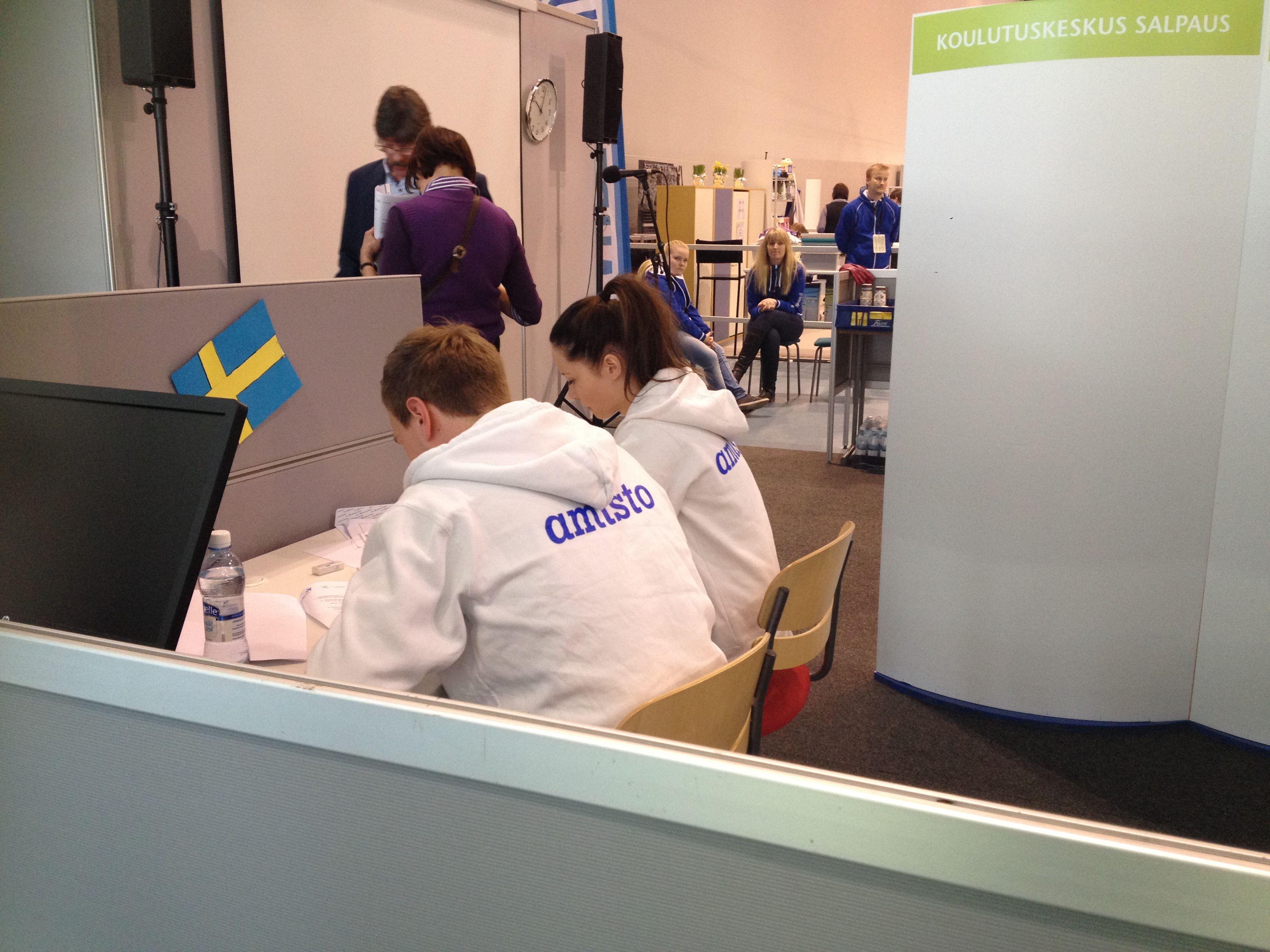 Porvoon ammattiopiston matkailukilpailijat Stegan Rogers ja Minttu-Maria Räsänen suorittamassa matematiikan laskenta tehtävää. Taustalla näkyy kilpailijoiden saattajia.