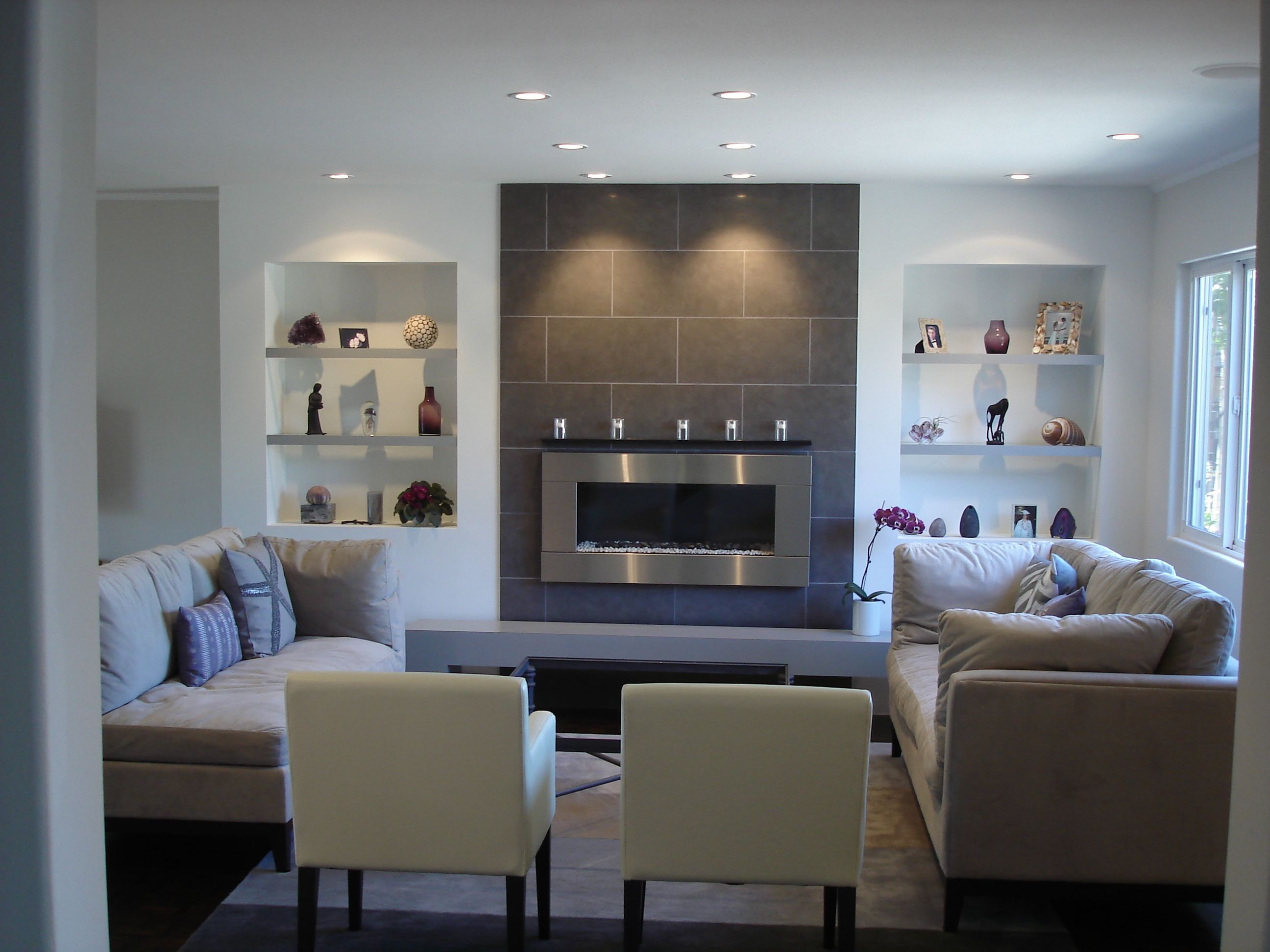 A clean contemporary living room featuring a wall mounted for Large modern fireplaces