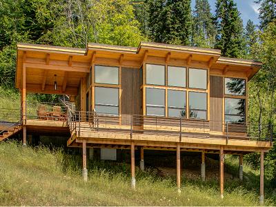 Este TimberCab 550 kit de casa se encuentra en Idaho lago Pend Oreille.  Los propietarios añaden una cubierta y porche extra para ampliar vida al aire libre en la ladera.  (Fine Construcción de viviendas)