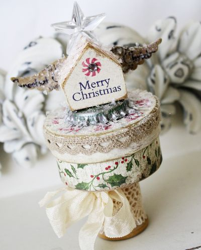 It all starts with a Wooden Spool wrapped in lace trim, a small paper mache box (to hold a present?), a vintage bottle cap, small wooden house, a trinket pin and then cover with Martha Stewart snow glitter!