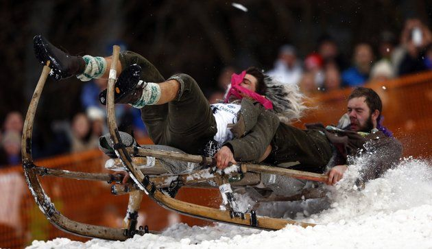 "Men land on a wooden sledge during a traditional Bavarian horn sledge race, known as ""Schnablerrennen"", in Gaissach near Bad Toelz January 27, 2013. The sledge race is an annual event to pay tribute to the traditional way of transporting hay, straw and wood down from the Alpine mountains to the valley. REUTERS/Michael Dalder"