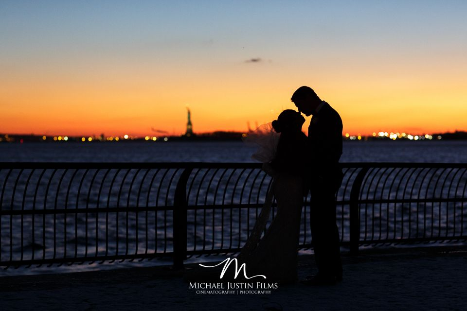 Sunset silhouettes of Bride and Groom by the Statue of Liberty
