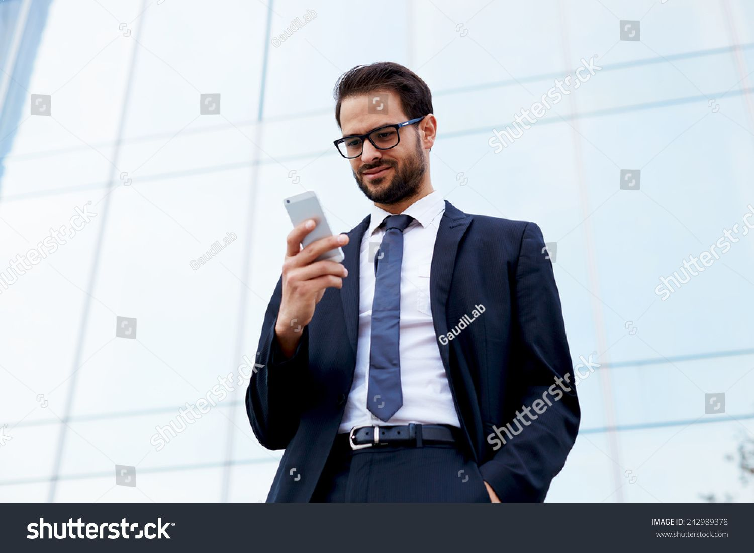 Happy Businessman Smiling As He Reads A Text Message Standing