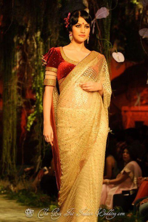 a23f2a706d8e3e A reddish-maroon velvet saree blouse worn with a gold designer saree.