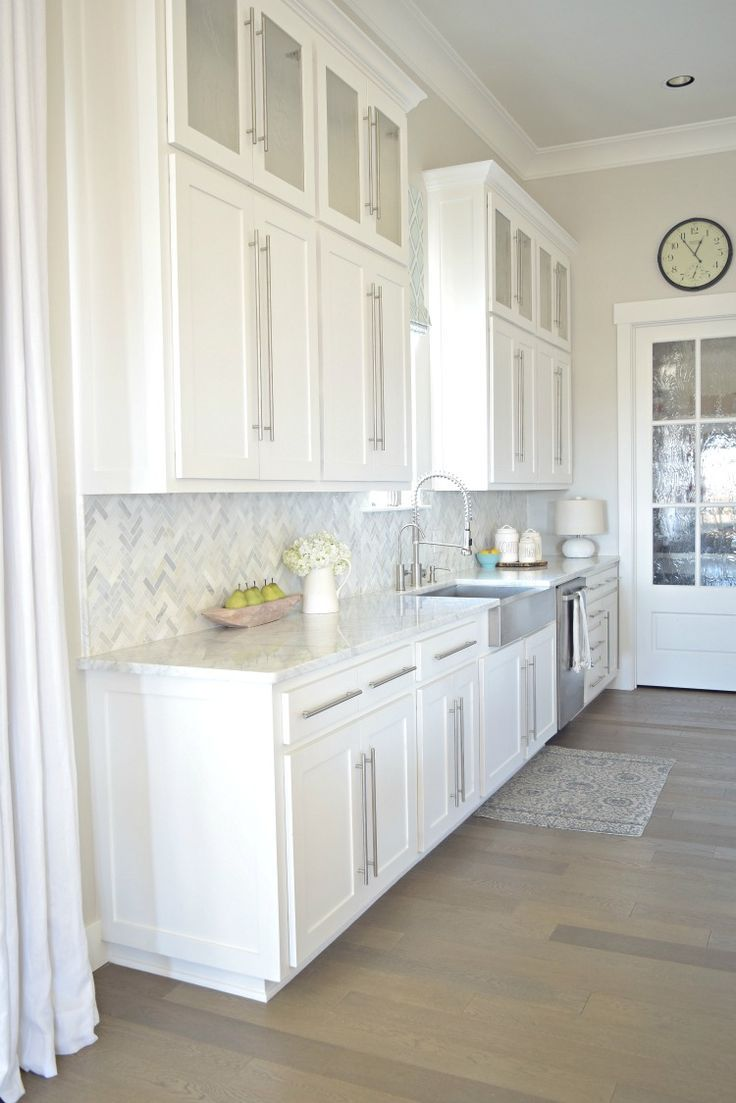 White kitchen stainless farmhouse sink herringbone backsplash