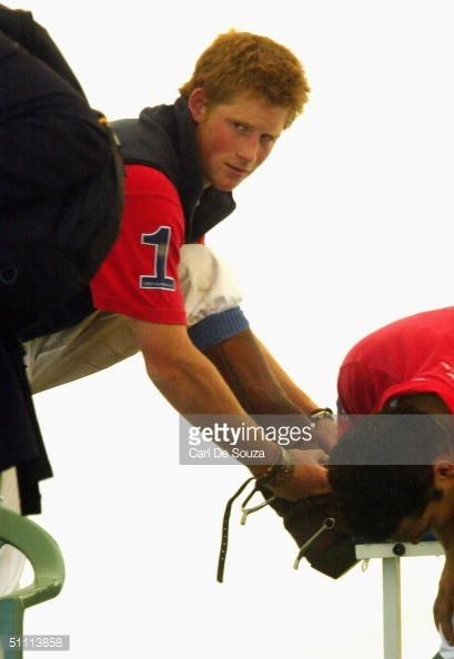 Prince Harry puts on his boots during polo at the Guards Polo Club,... News Photo | Getty Images