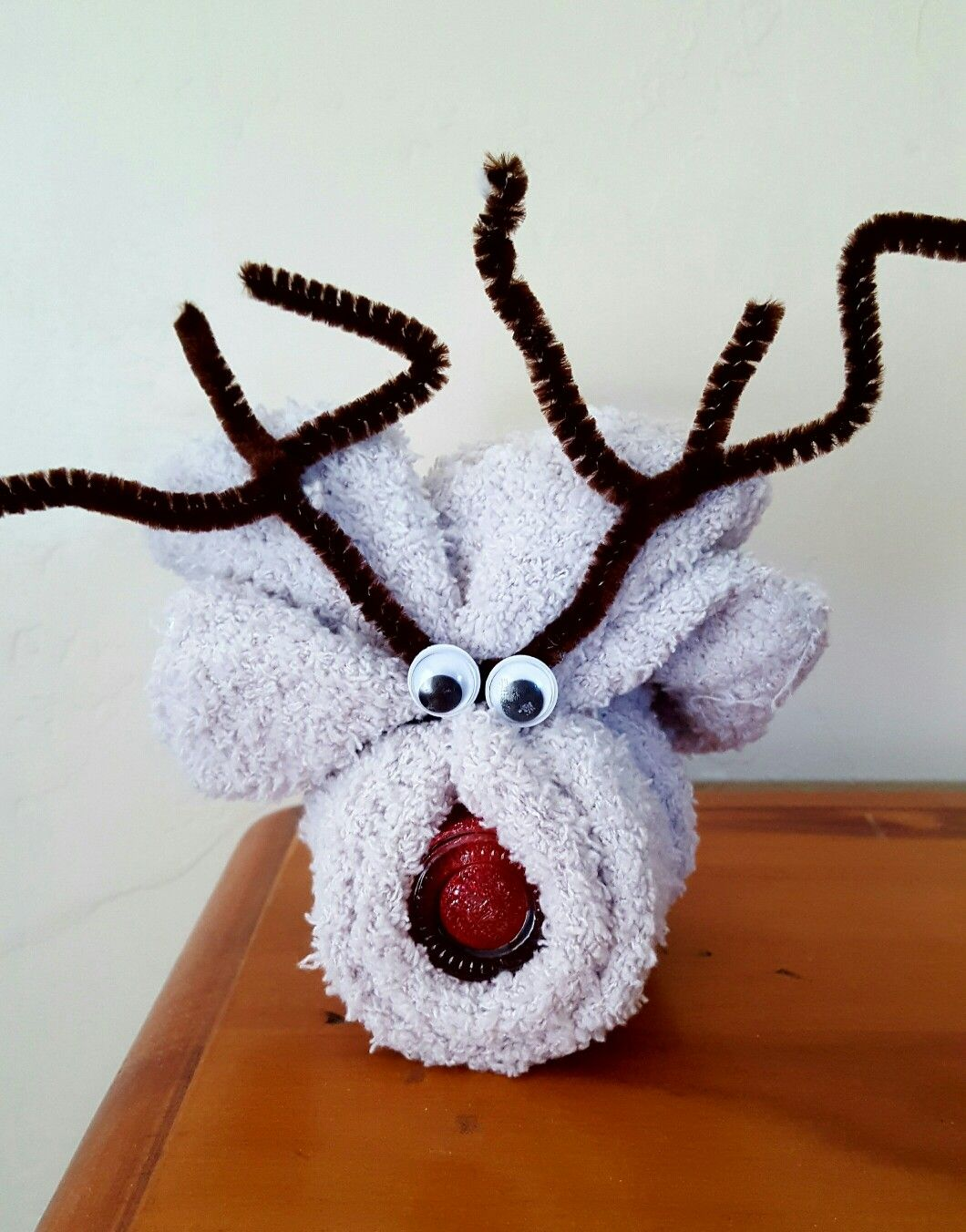 $2 Cheap Reindeer Christmas gift for girls or Young Women. Fuzzy socks and red nail polish from Dollar Tree. Wrap socks around polish, Twist the pipe cleaner around the socks. Done