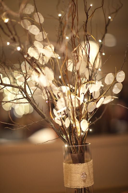 """Centerpiece: Per pinner... """"It is DIY. It was my wedding centerpiece- we used tall vases with rocks at the base. It's burlap around the base with a bracket jewel from a craft store. Then it's real branches, battery operated lit branches, and a fake silver dollar plant in the vase."""""""