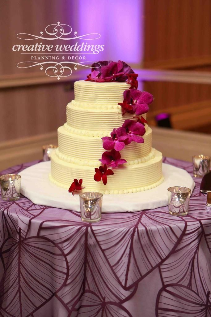 White wedding cake with purple orchids cascading down each layer ...