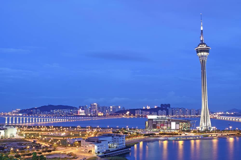 Urban landscape of Macau with famous traveling tower under sky near river in Macao Asia.