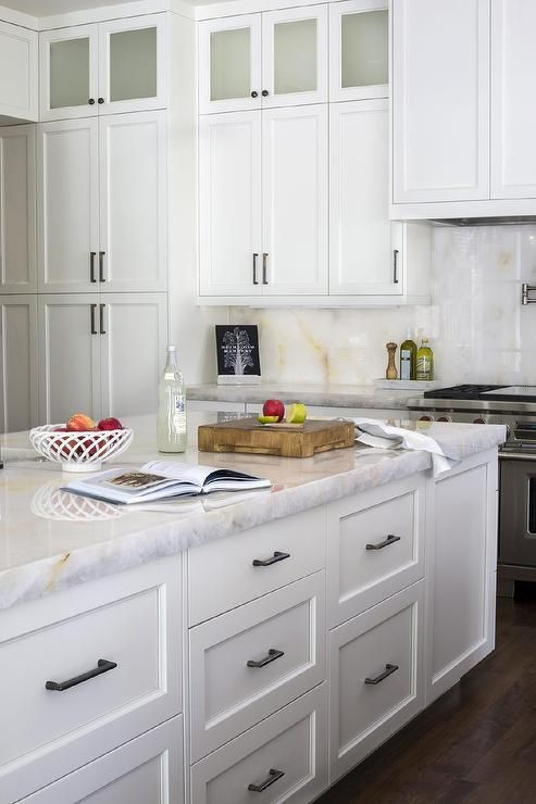 Beau Chic, White Kitchen Features Stacked White Shaker Cabinets Adorned With  Bronze Pulls And Knobs Paired With Gold And White Onyx Countertops And  Backsplash, ...