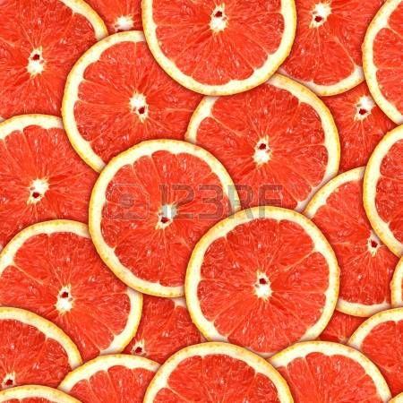 Fondo con rebanadas frescas de pomelo rojo.