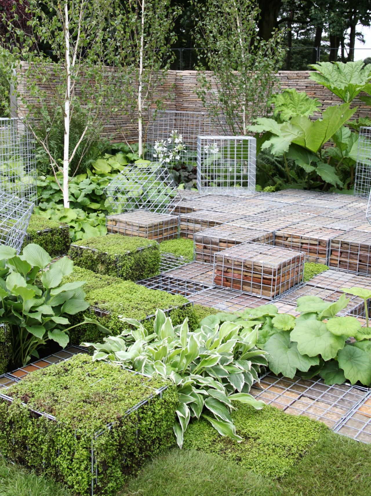 This modern garden uses gabions filled with stones and moss stacked next to hostas and other leafy plants for a unique, stylish look.