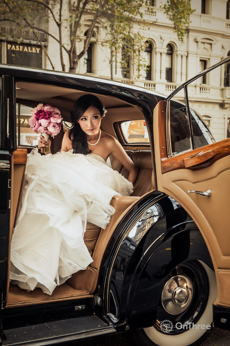 Bride stepping out of a black rolls royce vintage wedding