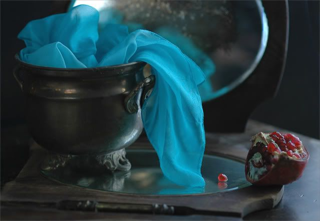 Still-life with turquoise scarf and a pomegranate.