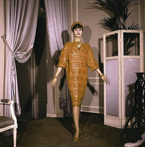 1958-59 Cocktail dress in orange satin entirely embroidered of glittering coral is by Yves St. Laurent for Christian Dior. The pert toque and the slippers are made of the same satin with assorted coral beads, Fall-Winter