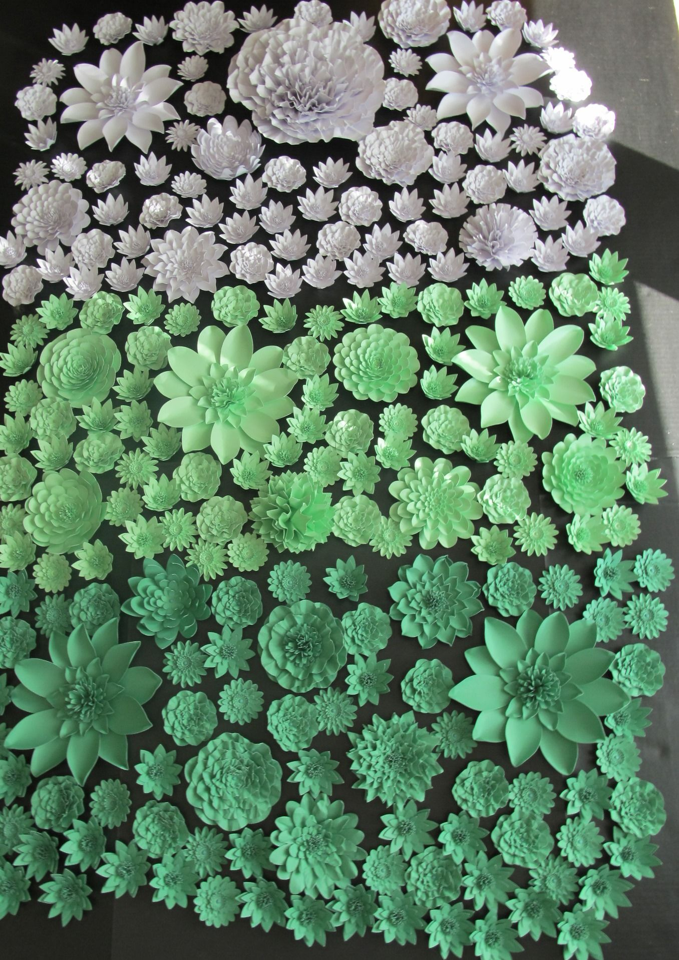 A wall of ombre paper flowers in mint greens and white