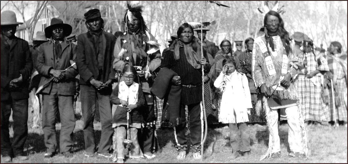 Red Cloud and a group of Sioux men and boys pose outdoors at Fort Robinson, Nebraska. Photo taken between 1874 and 1880.
