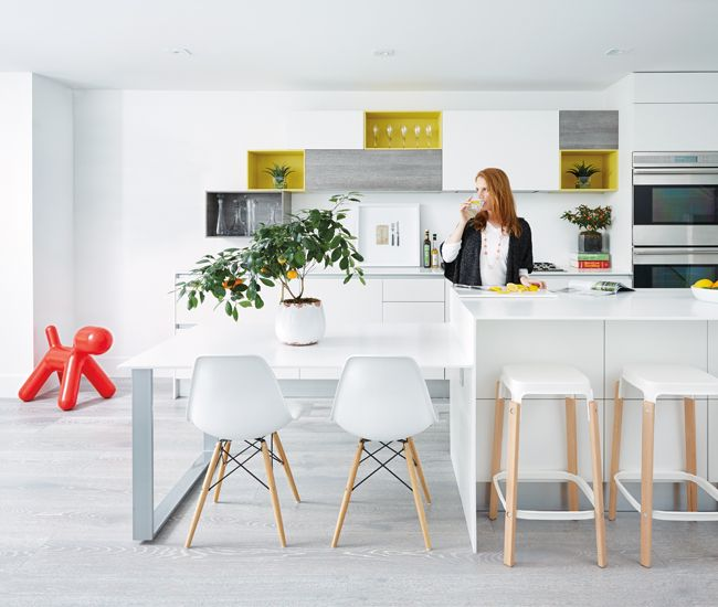 This scavolini kitchen boasts an island and counters topped with thin slabs of corian and chairs
