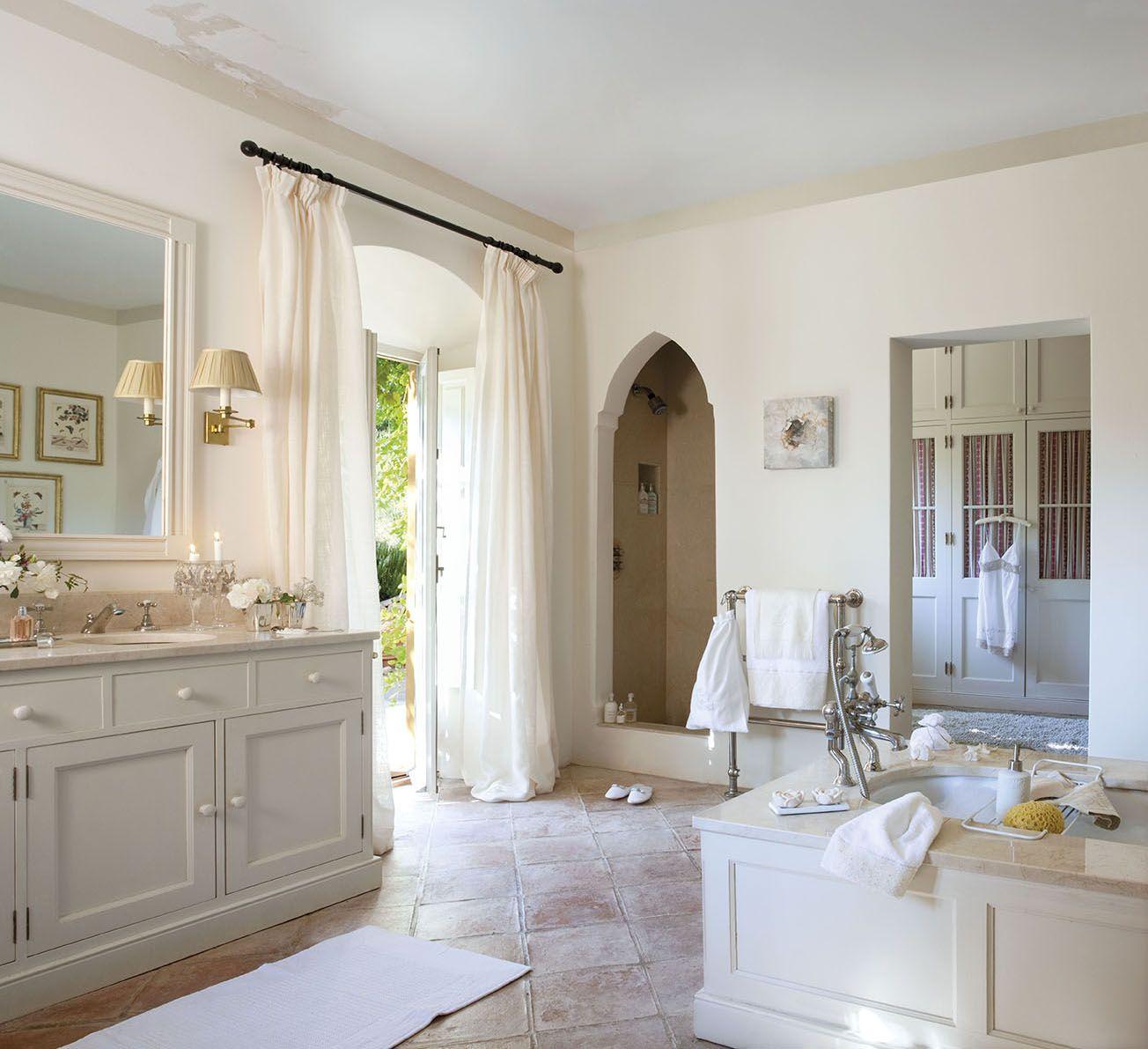 Amplio baño con bañera en la parte central, arco que comunica con el ...