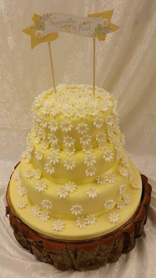 Three tier, pale yellow woodland wedding cake on tree stump stand ...