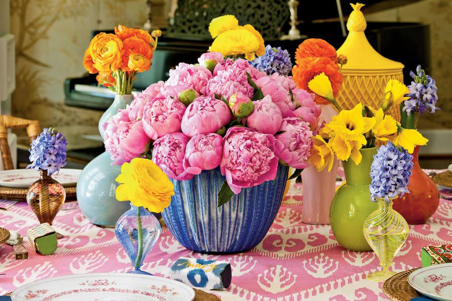 Create Vibrant Centerpieces - Bridal Luncheon Ideas: Showered in Color - Southernliving. Inspired by the hues of peonies, daffodils, hyacinths, and ranunculus, Kim created a palette of pink, yellow, blue, and orange, punctuated by lush centerpieces and new tablecloths made of ikat fabrics.