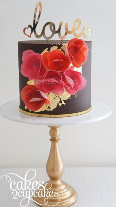 Chocolate covered ganache cake with edible gold leaf and wafer paper flowers