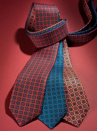 Elegantly hand printed and sewn English silk neckties, with an Edwardian printed square motif, left to right: C-fire with bottle; B-lagoon with green; A-peach with blue.