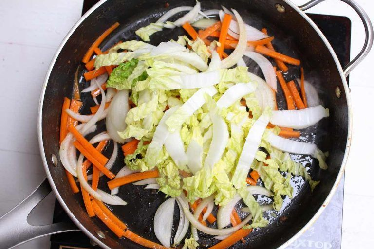 stir frying the vegetables when making singapore fried