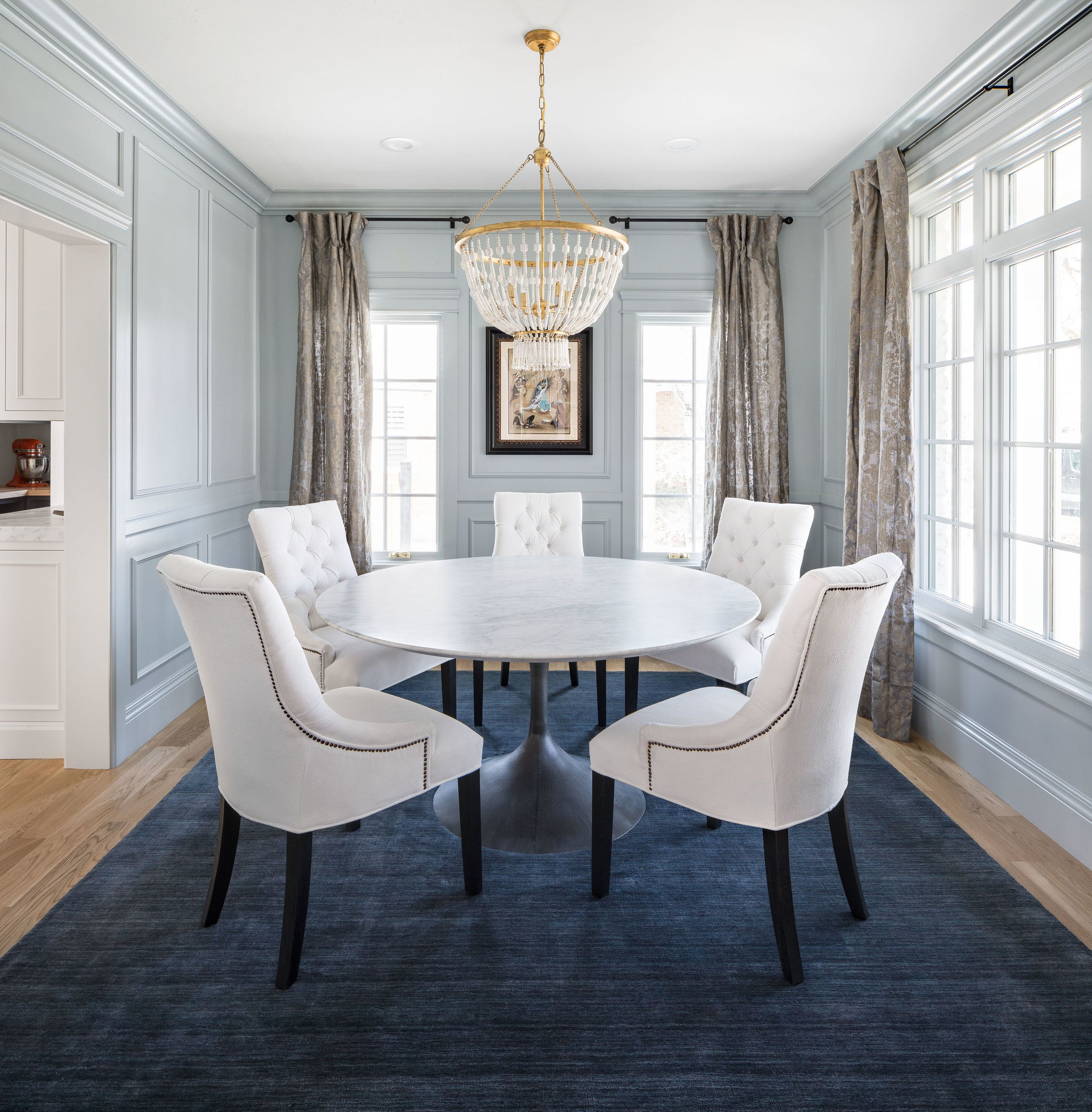 Traditional Dining Room Blue Area Rug Beaded Chandelier Round Dining Table White Upholstered Dining Room Blue Round Dining Room Table Round Dining Room