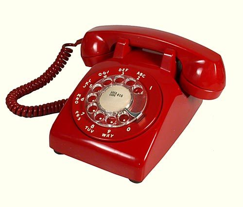 An iconic 1960's cherry red Northern Electric dial phone in working condition.