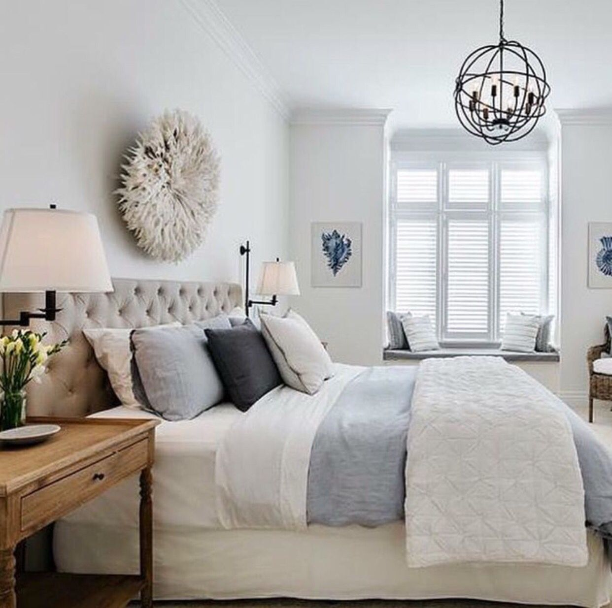 White bedroom with blue accents round feather art above bed home