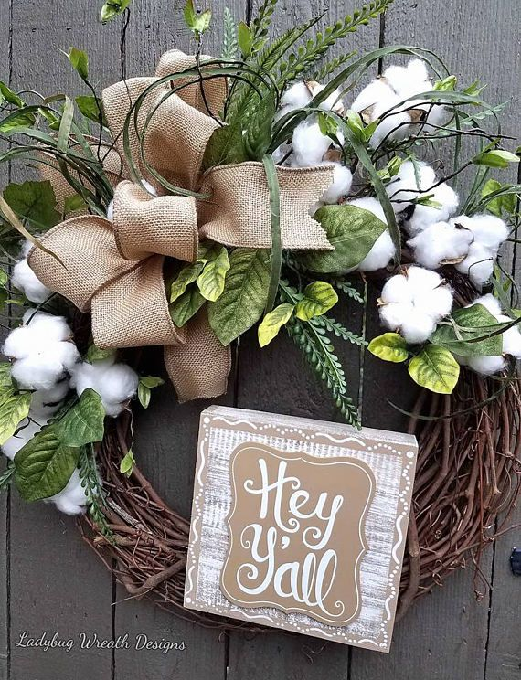 I love the natural rustic look of cotton & greenery in this wreath. It truly adds warmth to your home and with the Hey Yall wooden sign, it would welcome anyone into your house. The cotton bolls are nestled among the natural greenery. The natural colored faux burlap bow completes this design. This wreath is designed on an 18 grapevine wreath, completed it measures 24 x 22 Only one available & ready to be shipped. Please favor my shop here & check out other designs on my Facebook...