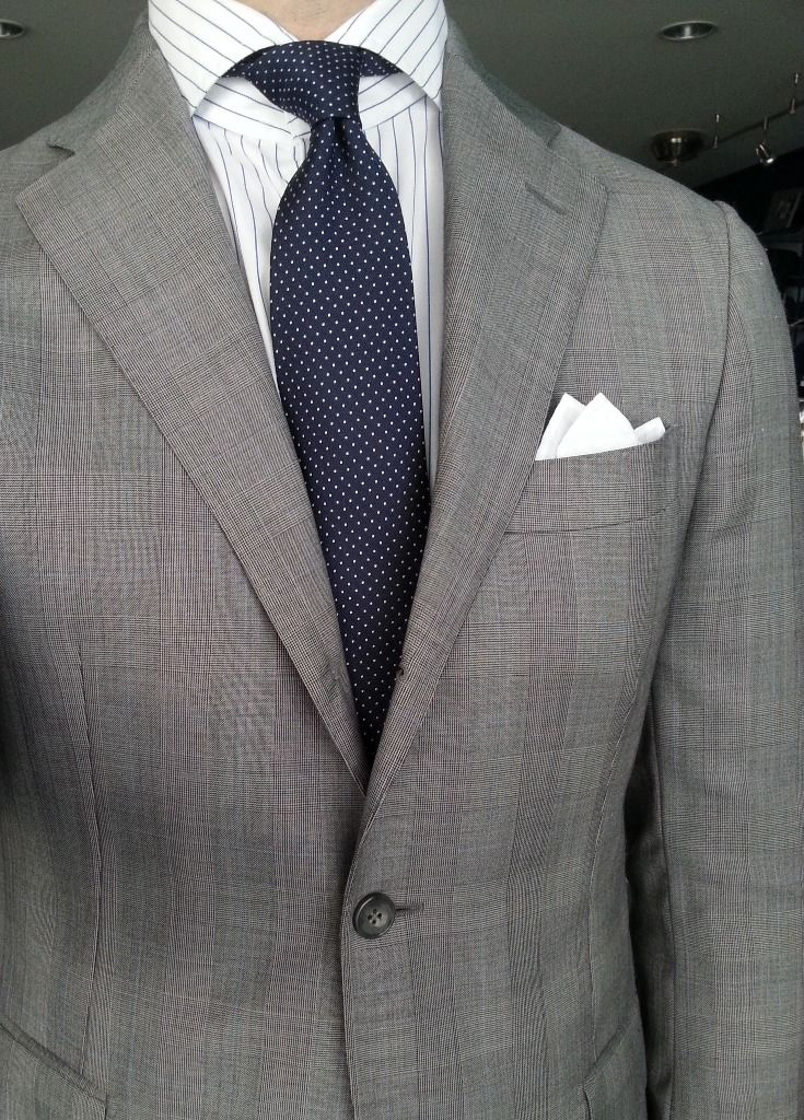 Light grey suit, white shirt with blue wide pinstripes, navy tie with white pin dots
