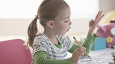 Young girl working on math homework counting on her fingers | Understanding Dyscalculia