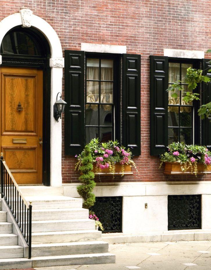 Black windows on brick with doorway arch Red brick house