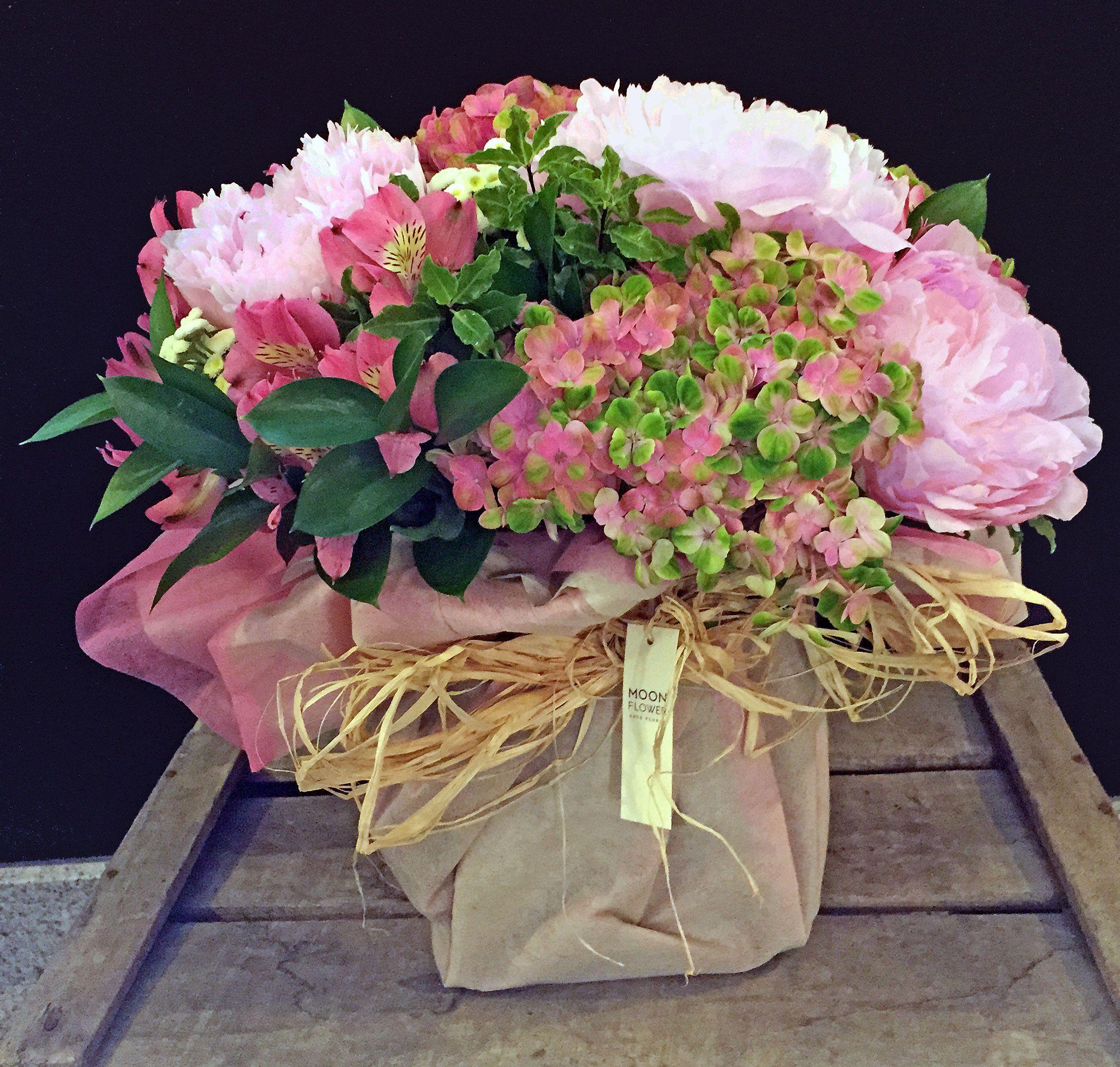 Centro con flores variadas en tonos rosas y verdes.