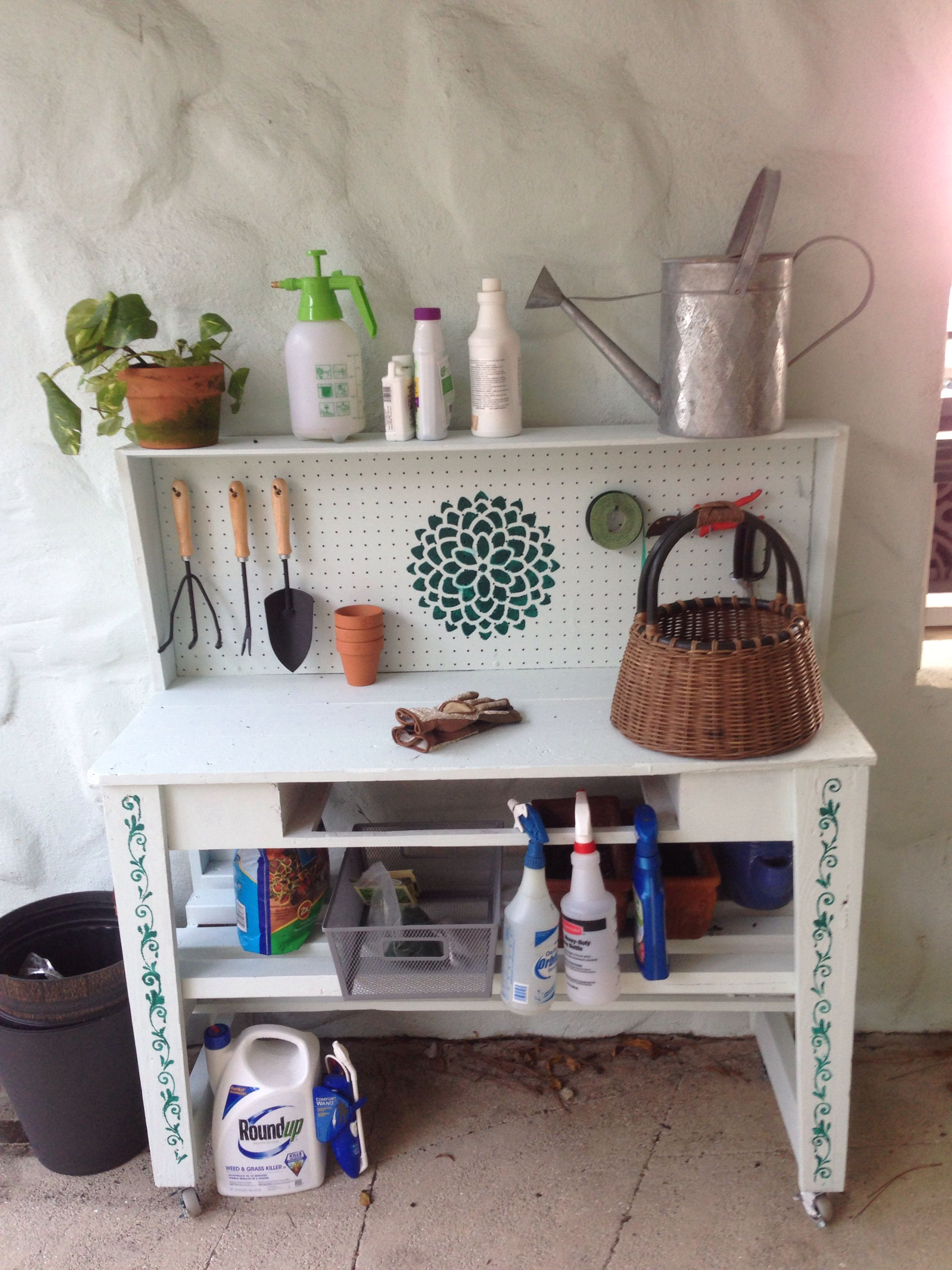 Potting bench. Rescued neighbor's work bench from rubbish. added vented shelves, painted and stenciled it and added hooks for organizing tools.