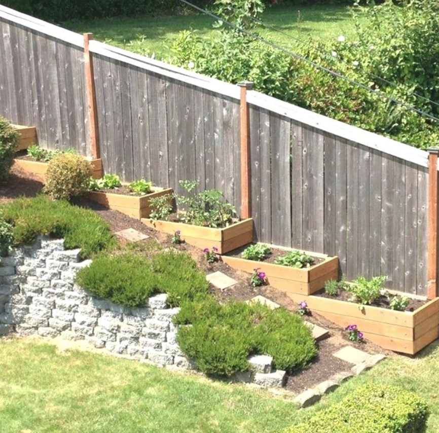 Terraced backyard with fence. Like the planter boxes ...