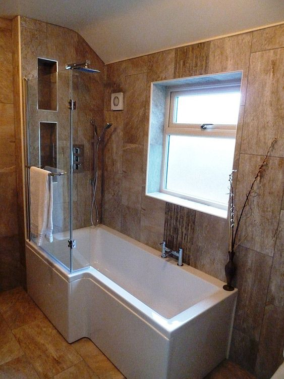 built in tub and shower. Double shower fully tiled in stone with built shelving feature and  bath