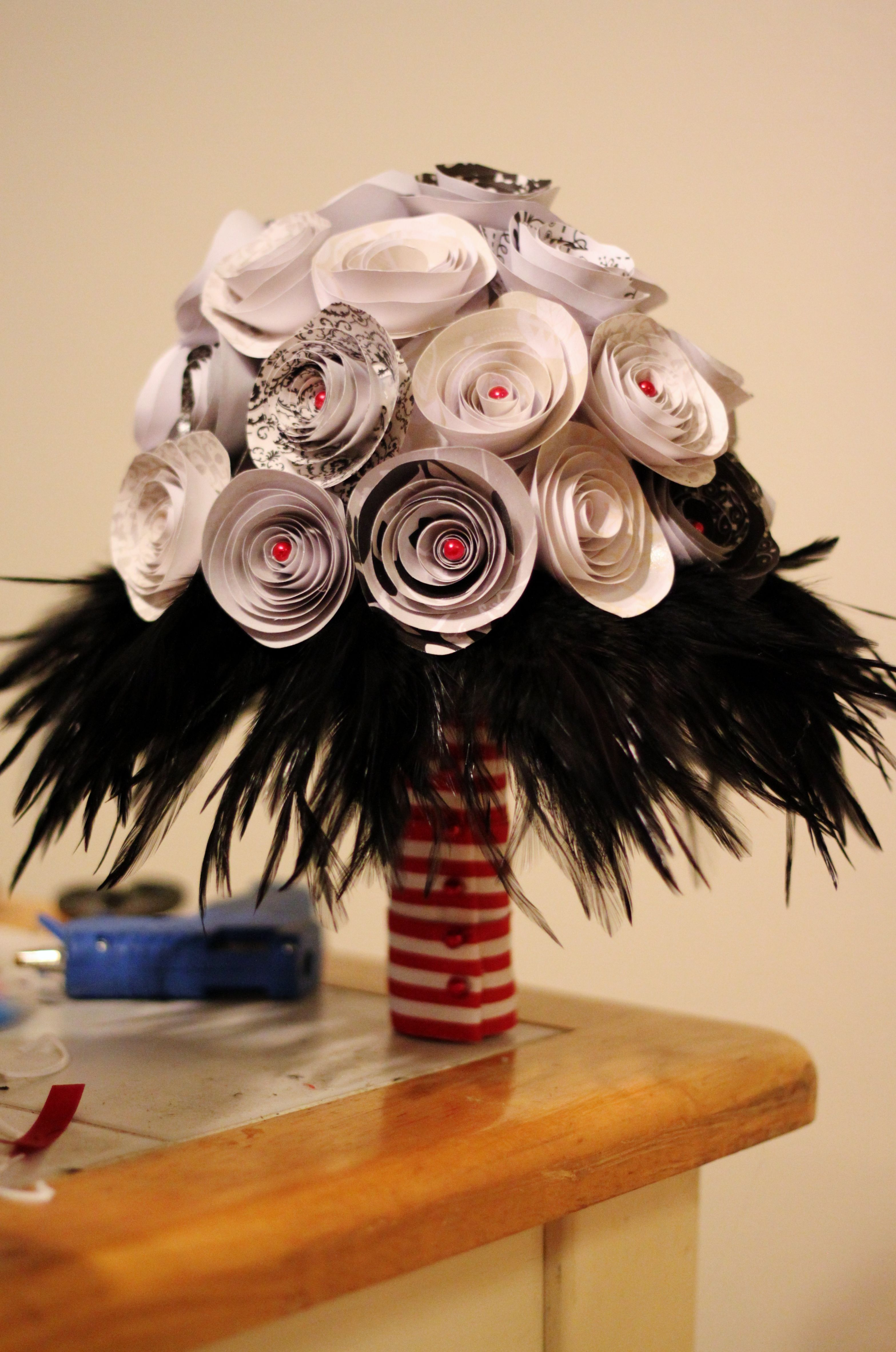 This is my finished bouquet! Rolled black and white paper flowers with red pearl beads in the centers arranged on a styrofoam bouquet holder. The black feathers are trim glued to a large bouquet collar I ripped the white lace trim off of. I thicken the handle by wrapping some sheet foam around it and covering it with pretty red/white striped ribbon. I love how it came out!! =]