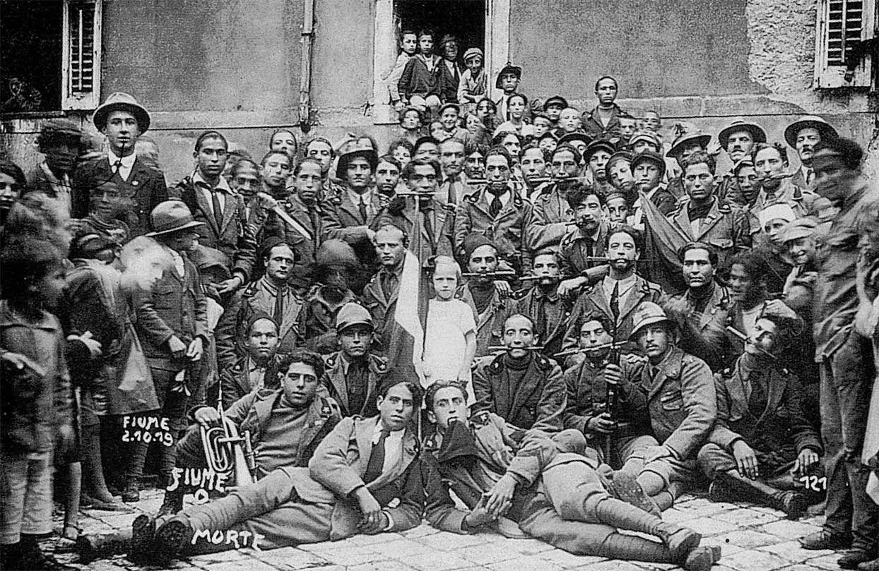"""Debitore, poeta e guerriero si fusero in uno: egli decise l'impresa. Il 12 settembre 1919, con un reparto di 'arditi' e con due battaglioni dell'esercito, [D'Annunzio] occupò Fiume, senza colpo ferire. [...] Mussolini nel suo giornale commentò: """"D'ora innanzi la capitale d'Italia è Fiume"""". Ufficiali a spasso, 'arditi', nazionalisti, studenti, 'volontaristi', disoccupati, futuristi e poeti gridavano ammirati: """"Questà è politica!"""" Tutti accorrevano a Fiume. (I, 18)"""