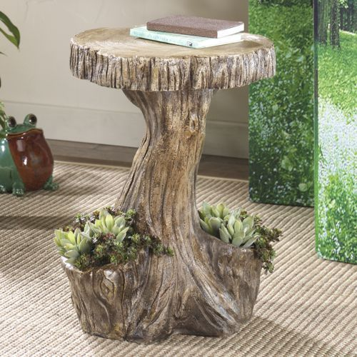 "Table, Tree Planter- Crafted to look like a tree trunk and topped by a larger slice of ""timber,"" this table is a little touch of the forest. Two planter pockets at the base (4 1/2"" diam. x 4 1/2"" d) create space for small potted plants to nestle among the roots. Resin. 15"" w x 20"" h x 13 1/2"" d. Available only in brown."