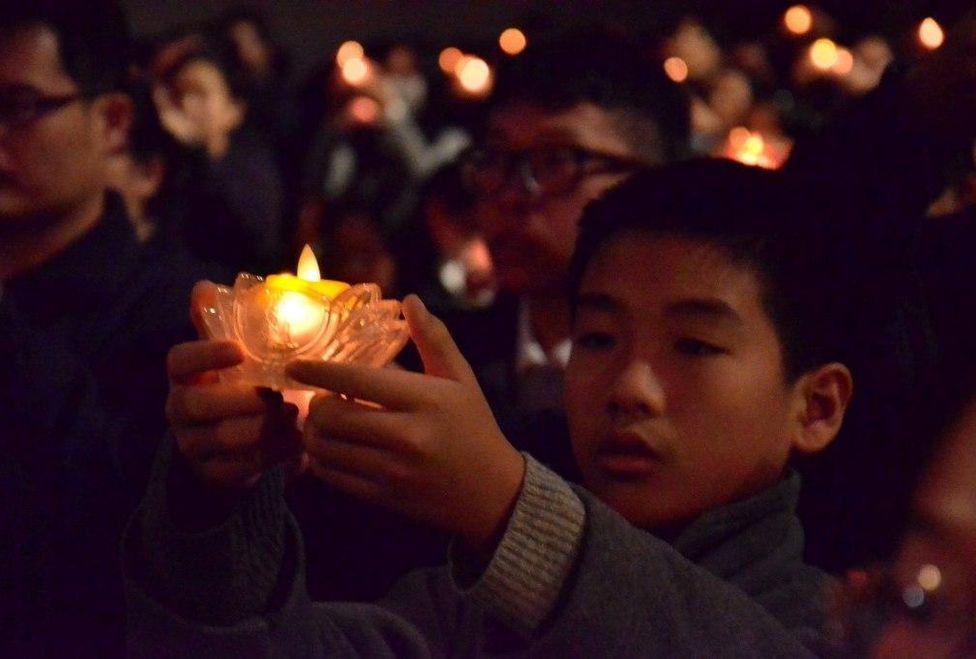 Taiwan, un niño reza y enciende una vela , en honor de las victimas del terremoto el Hualien en 06 del02 de 2018.