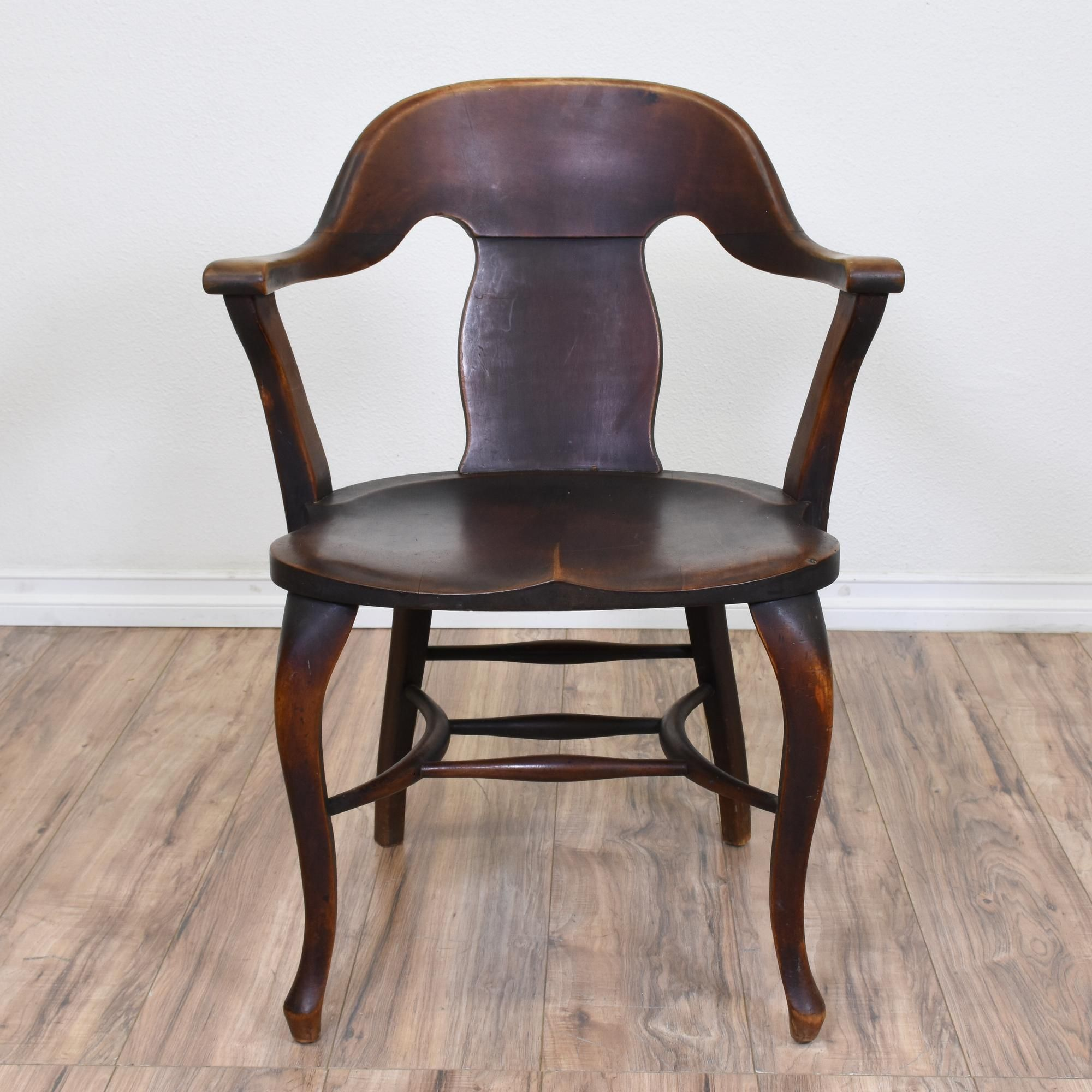 This rustic antique banker s chair is featured in a solid wood