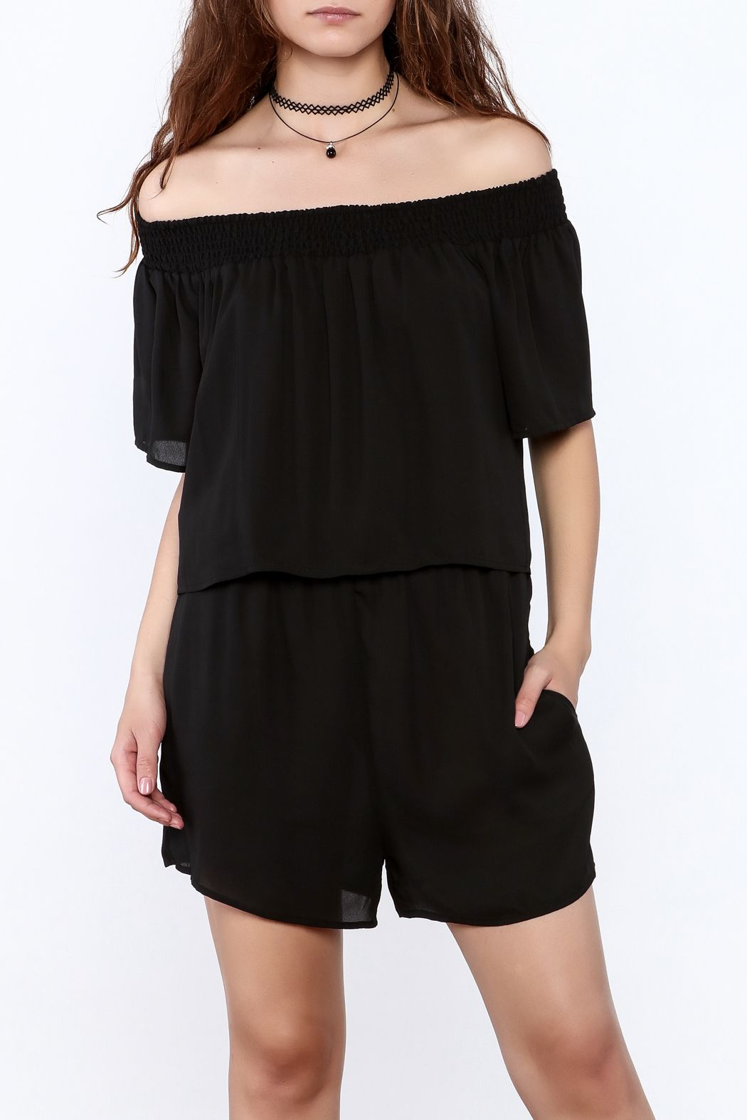 6e7d0eefd938 Black double layer flowy romper with off-shoulder short sleeves and functional  pockets. Smocked shoulder band. Black Flowy Romper by Dora Landa.