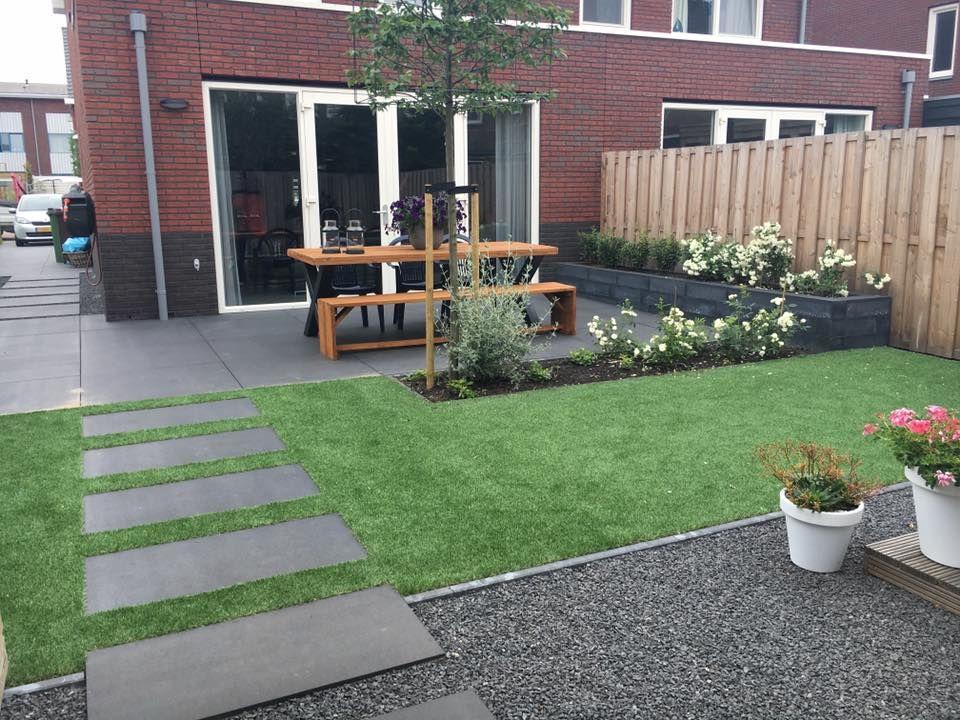 Kindvriendelijke tuin met kunstgras en grote tegels landscaping