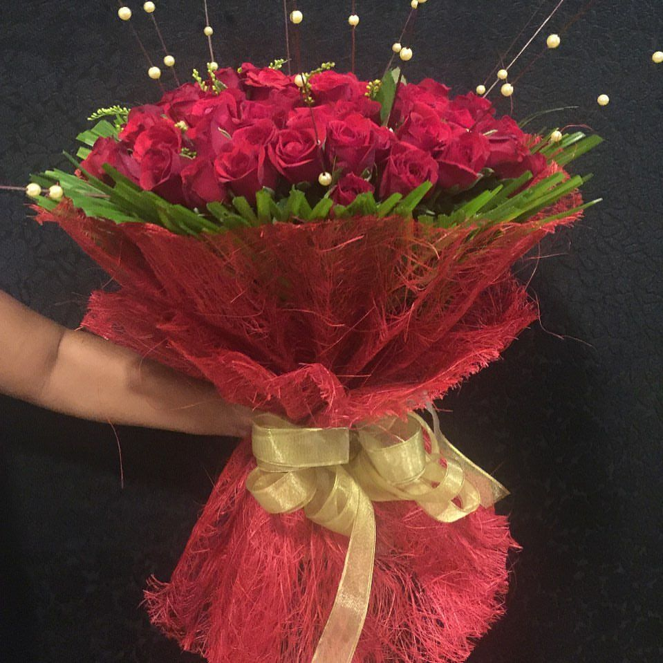 50 red roses flower bouquet in a red netted jute wrap & a