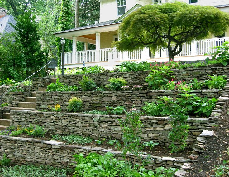 Hillside landscaping tiering an existing rock wall for Hillside landscaping