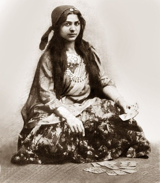 Gypsy woman in a folk costume, using a normal deck of playing cards to make predictions